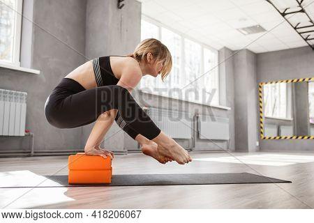 Sportswoman Balancing On Her Hands On Yoga Blocks, Doing Yoga At Sport Studio, Copy Space