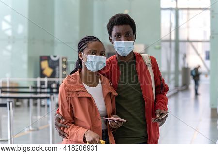 Portrait Of Happy Black Couple In Medical Mask Hold Boarding Pass And Passports In Airport In Covid-