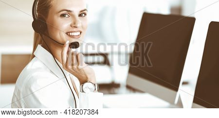 Blond Female Customer Service Representative Is Consulting Clients Online Using Headset. Call Center