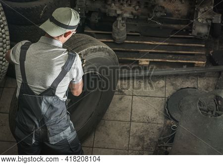 Caucasian Automotive Worker In His 40s Replacing Heavy Duty Truck Wheel For The New One. Semi Truck
