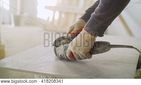 The Master Cuts The Tiles On An Angle Grinder With A Special Diamond Disc. Cutting Large Ceramic Til