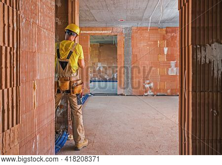 Professional Construction Worker Inside Brick Built Building Finishing Wall Elements. Construction I