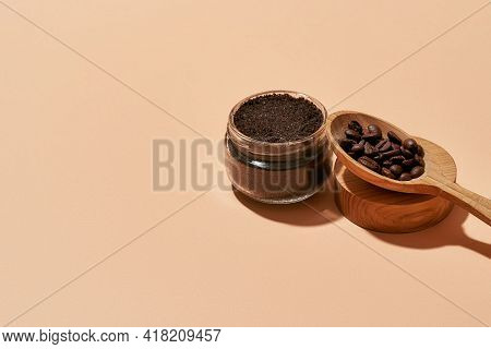 Cosmetological Scrub In Open Can Beside Wooden Spoon Filled With Coffee On Light Orange Background W