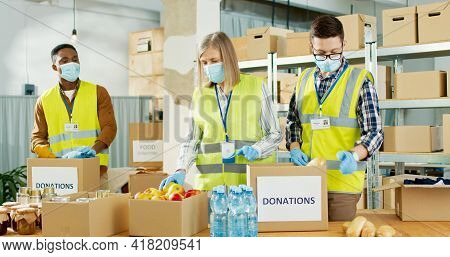 Mixed-race Different Senior And Young Charity Workers In Medical Masks Working In Shipping Charitabl