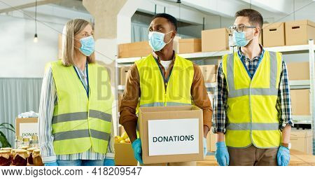 Portrait Of Multi-ethnic Happy Senior And Young Male And Female Charity Workers In Medical Masks In
