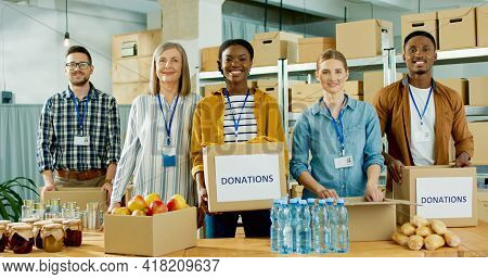 Cheerful Young And Senior Multi-ethnic Charity Organization Workers Males And Females Work At Charit