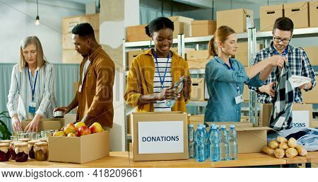 Mixed-race Happy Diverse People Men And Women Working At Charity Organization Sorting And Packing Do