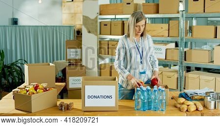 Mature Caucasian Pretty Female Warehouse Worker Volunteer Working In Shipping Delivery Charitable St