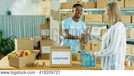 Happy African American Young Handsome Man Volunteer Smiling Working At Charity Center Giving Food To
