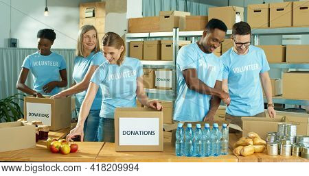 Mixed-race Happy Positive Male And Female Different Volunteers Working In Charity Organization Cente