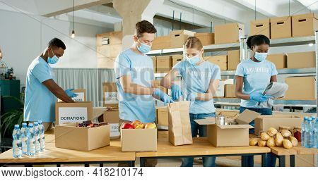Group Of Caucasian And African American Male And Female Volunteers Putting Food In Packet In Shelter