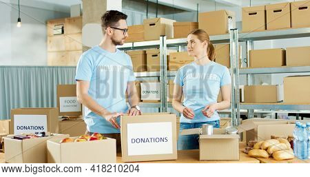 Caucasian Young Male And Female Volunteers Putting Food Products In Box Sorting Donations Parcel Wor