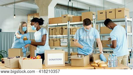 Diverse Mixed-race People Working In Warehouse Collecting Donations Preparing Social Help Boxes And
