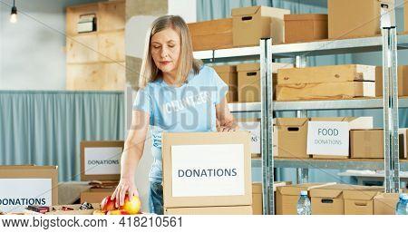 Portrait Of Cheerful Beautiful Caucasian Senior Female Volunteer Alone Working In Charitable Deliver