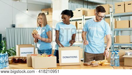 Busy African American And Caucasian Female And Male Volunteers Preparing Donations Box, Packing Food