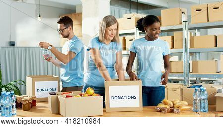 Mixed-race Joyful Male And Female Food Bank Volunteers Putting Food Products In Donation Box Working