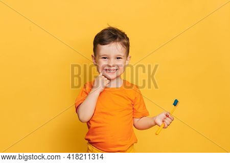 Happy Baby Toddler Boy Brushing His Teeth With A Toothbrush On A Yellow Background. Health Care, Ora