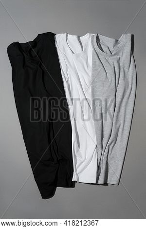 Flat Lay Of Three Monochrome Cotton T Shirts Mock Up Lying Vertically On Gray Background. Clothes, M