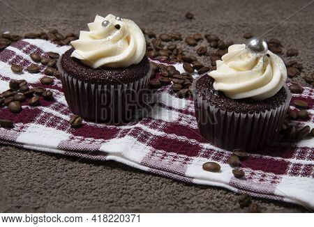 Two Homemade Cupcakes And Coffee Beans On Brown Cloth Background, Homemade Cake With Cream