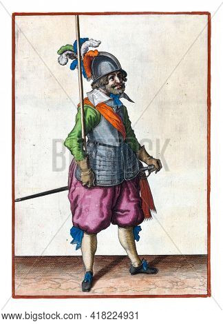 A full-length soldier holding a spear (lance) in his right hand leaning against his right arm vertically