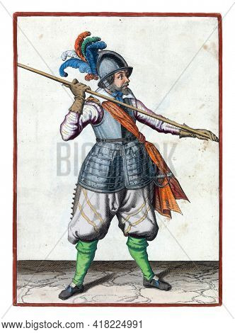 A soldier, full-length, carrying a spear (lance) above his right shoulder, the point pointing obliquely towards the ground. His hands wide apart on the skewer