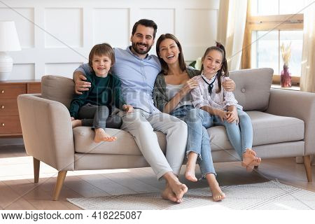Portrait Of Happy Family With Children Relax On Sofa