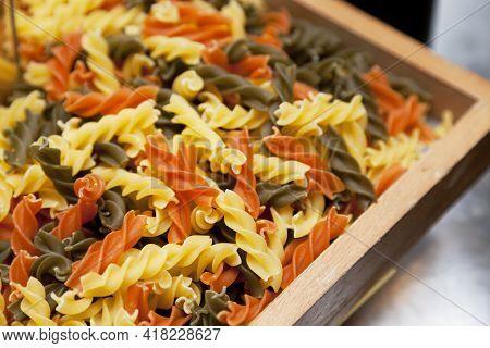 Raw Homemade Tricolor Fusilli Pasta In A Basket.