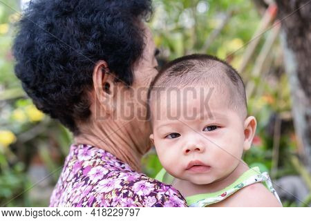 Adorable Baby Boy Looking At Camera With Interest On Shoulder Of Grandmother. Little Asian Newborn L