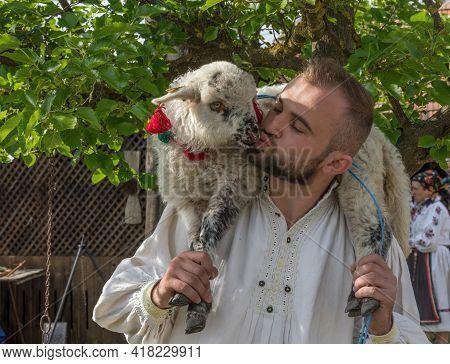 Salaj, Transylvania, Romania-may 14, 2018: Young Man In Traditional Romanian Folk Costume Holding An