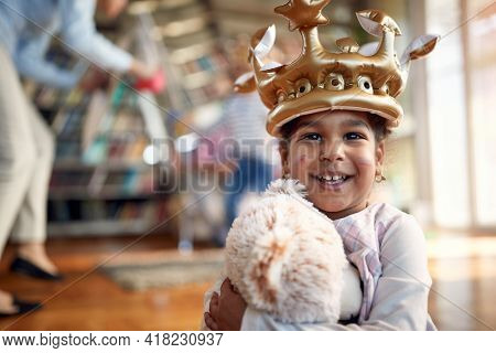 A charming little girl with a cute smile posing for a photo in a cheerful atmosphere at home while enjoying with her family. Family, together, love, playtime