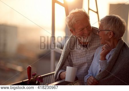 An elderly couple having a good time together on the terrace of their apartment at a beautiful sunset. Spouses, pensioners, together, home
