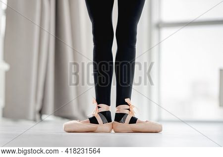 Closeup view of ballerina straightened legs staying in first position during dance class in choreography studio