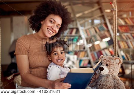 A young beautiful mother and her little daughter posing while sitting on the swing in a relaxed atmosphere at home together. Family, together, leisure