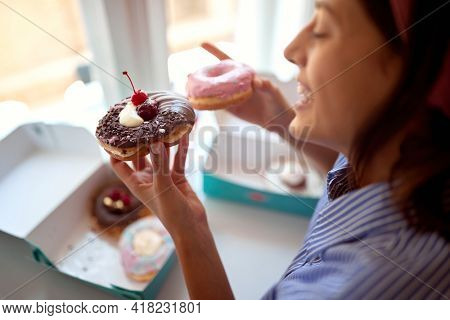 A young girl in a pleasant atmosphere in a pastry shop is holding delicious donuts in her hands which she is going to eat with a pleasure. Pastry shop, dessert, sweet