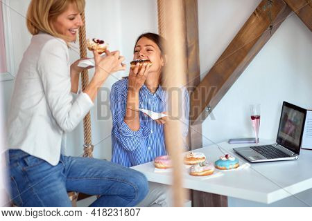 Two female friends in a pastry shop are passionately eating delicious donuts of irresistible appearance. Pastry shop, dessert, sweet