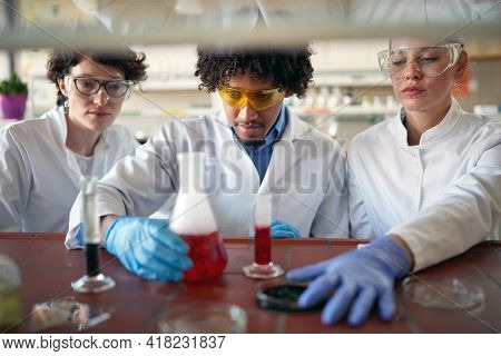 Young chemistry students are concentrated on work with chemicals in a working atmosphere in the university laboratory. Science, chemistry, lab, people