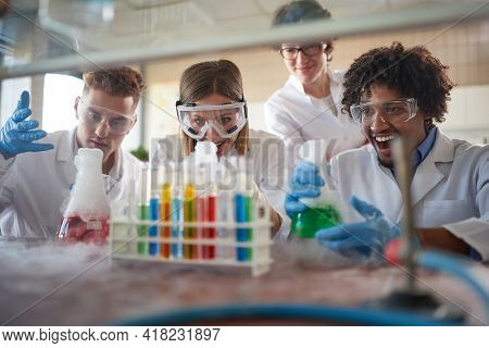 Young chemistry students in a laboratory relaxed atmosphere are excited while watching colorful chemical reactions. Science, chemistry, lab, people