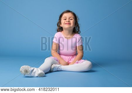 Beautiful And Funny Little Girl, Ballerina In Pink Dress Posing To Camera While Relaxing On Blue Bac