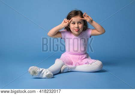 Isolated Portrait Over Blue Background Of An Adorable Preschool Girl Ballerina Grimacing And Showing