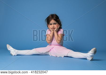 Cute Ballerina In Pink Dress Perfecting Twine While Sitting On Blue Background With Copy Space