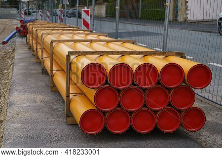Stacks Of Orange-yellow Pvc Electrical Conduit Pipes. Construction Site.