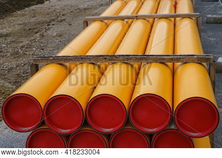 Construction Site. Stacks Of Orange-yellow Pvc Electrical Conduit Pipes.