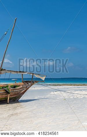 Wooden Boat At The Beach From Zanzibar With Stunning Turquoise Water And Copy Space For Text, Vertic