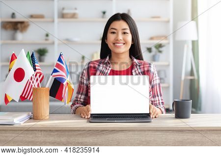 Online Language Courses. Happy Asian Woman With Laptop And International Flags, Mockup
