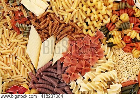 Selection of dried Italian pasta types with tricolour and whole wheat shapes. Healthy carbohydrate food concept. Abstract background, flat lay, top view.
