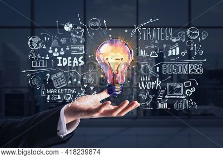 Businessman Hand Holding Hologram Of Colorful Light Bulb As A Concept Of New Idea For Start Up. Conc