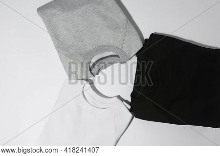Three Perfectly Folded Monochrome Sweatshirts Gray, Black And White Laid Out In A Circle Isolated Ov