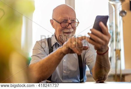 Shot of a senior man using a mobile phone at home