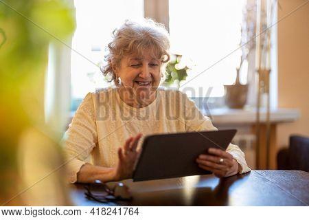 Happy senior woman using digital tablet at home