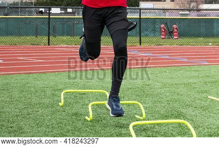 Front View Of A High School Runner Bounding On One Leg Over Six Inch Yellow Banana Mini Hurdles Duri